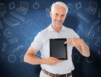 Composite image of mature student showing tablet pc. Mature student showing tablet pc against blue chalkboard Royalty Free Stock Photography