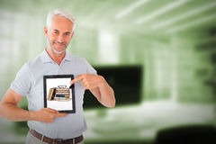 Composite image of mature student showing tablet pc. Mature student showing tablet pc against digital image of workplace Royalty Free Stock Photo