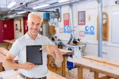 Composite image of mature student showing tablet pc. Mature student showing tablet pc against workshop Royalty Free Stock Photos