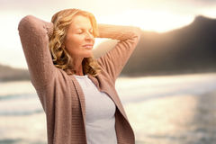 Composite image of mature woman stretching with eyes closed. Mature woman stretching with eyes closed   against mountain against sky at beach Royalty Free Stock Photography