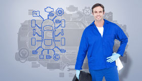 Composite image of mechanic holding tire while standing with hand on hip Royalty Free Stock Photo