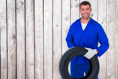 Composite image of mechanic holding tire on white background Royalty Free Stock Photos