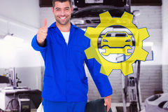 Composite image of mechanic with tire gesturing thumbs up. Mechanic with tire gesturing thumbs up against auto repair shop Royalty Free Stock Image