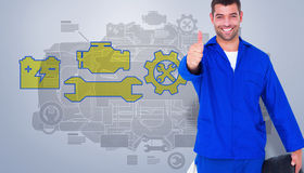 Composite image of mechanic with tire gesturing thumbs up. Mechanic with tire gesturing thumbs up against grey vignette Royalty Free Stock Image
