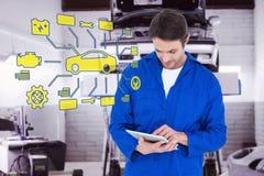 Composite image of mechanic using digital tablet over white background. Mechanic using digital tablet over white background against auto repair shop Stock Photography