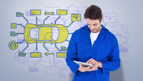 Composite image of mechanic using digital tablet over white background Royalty Free Stock Photos