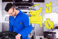 Composite image of mechanic working on tire Stock Photo