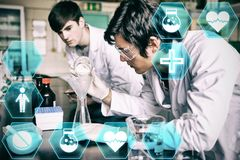 Composite image of medecine. Medecine against male chemistry students making an experiment Stock Images