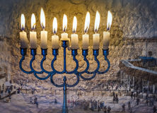 Composite image of menorah with glittering candles and western wall in Jerusalem. Royalty Free Stock Images