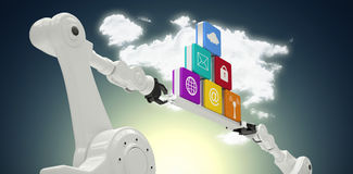Composite image of metallic robotic hands holding computer icons against dark grey vignette Royalty Free Stock Image