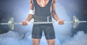 Composite image of mid-section of bodybuilder lifting heavy barbell weights Royalty Free Stock Photo