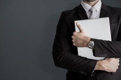 Composite image of mid section of businessman holding computer. Mid section of businessman holding computer against grey background stock photo