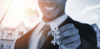 Composite image of mid section of businessman showing new house key. Mid section of businessman showing new house key against bulldozer by building at Stock Photography