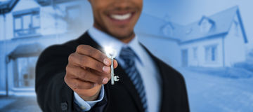 Composite image of mid section of businessman showing new house key. Mid section of businessman showing new house key against paved footpath outside building Stock Photography