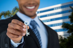 Composite image of mid section of businessman showing new house key. Mid section of businessman showing new house key against tree by glass building Stock Photos