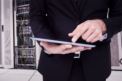 Composite image of mid section of a businessman touching digital tablet. Mid section of a businessman touching digital tablet against data center Stock Photography