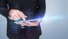 Composite image of mid section of a businessman touching digital tablet. Mid section of a businessman touching digital tablet against grey vignette Stock Photo