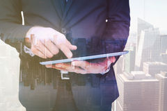 Composite image of mid section of a businessman touching digital tablet. Mid section of a businessman touching digital tablet against mirror image of city Stock Photo