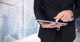 Composite image of mid section of a businessman touching digital tablet Stock Image