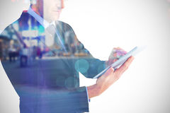 Composite image of mid section of a businessman using digital tablet Royalty Free Stock Image