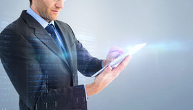 Composite image of mid section of a businessman using digital tablet Stock Photo