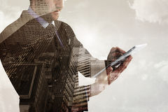 Composite image of mid section of a businessman using digital tablet Stock Image