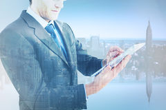 Composite image of mid section of a businessman using digital tablet Stock Photography