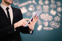 Composite image of mid section of a businessman using digital tablet pc Royalty Free Stock Photography