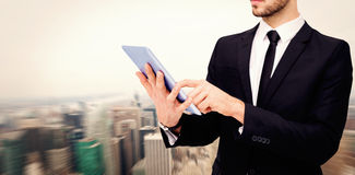 Composite image of mid section of a businessman using digital tablet pc Stock Image