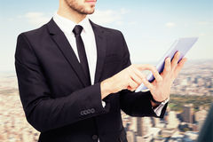 Composite image of mid section of a businessman using digital tablet pc Stock Photography