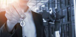 Composite image of mid section of businesswoman showing house key. Mid section of businesswoman showing house key against businesspeople forming huddle in office royalty free stock images