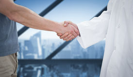 Composite image of mid section of a doctor and patient shaking hands Royalty Free Stock Photos