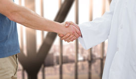 Composite image of mid section of a doctor and patient shaking hands Royalty Free Stock Photo