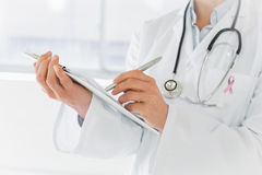 Composite image of mid section of a female doctor writing reports Stock Images