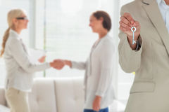 Composite image of mid section of female executive showing new house key. Mid section of female executive showing new house key against women and therapist Stock Photography