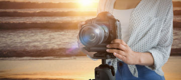 Composite image of mid section of female photographer with digital camera. Mid section of female photographer with digital camera  against image of a sunset over Royalty Free Stock Image