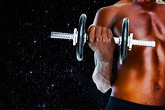 Composite image of mid section of fit shirtless man holding dumbbell Stock Photography
