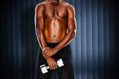 Composite image of mid section of fit shirtless man holding dumbbell Royalty Free Stock Images