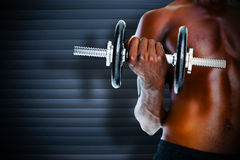 Composite image of mid section of fit shirtless man holding dumbbell Stock Image