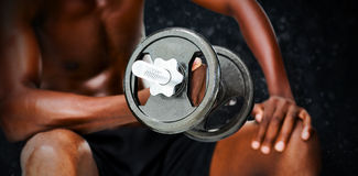 Composite image of mid section of fit shirtless man lifting dumbbell Royalty Free Stock Photo