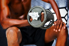 Composite image of mid section of fit shirtless man lifting dumbbell Stock Photo
