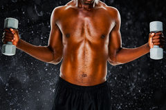 Composite image of mid section of fit shirtless man lifting dumbbells. Mid section of fit shirtless man lifting dumbbells against black background Stock Images