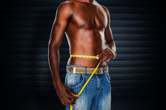 Composite image of mid section of a fit shirtless man measuring waist Royalty Free Stock Photo