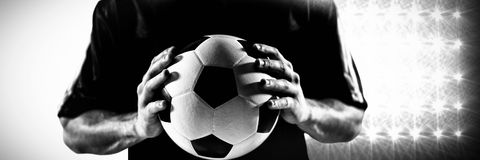 Composite image of mid section of football player in black jersey holding ball. Mid section of football player in black jersey holding ball against spotlight Royalty Free Stock Images