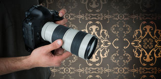 Composite image of mid section of male photographer holding digital camera Stock Image