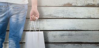 Composite image of mid section of man carrying shopping bag Stock Image