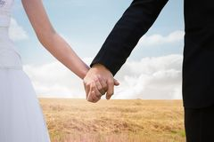 Composite image of mid section of newlywed couple holding hands in park Royalty Free Stock Photography