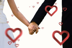 Composite image of mid section of newlywed couple holding hands in park Stock Photo