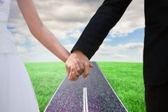 Composite image of mid section of newlywed couple holding hands in park Royalty Free Stock Images