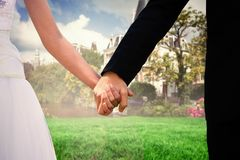 Composite image of mid section of newlywed couple holding hands in park Stock Photography